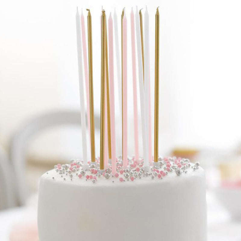 a set of long, rose and gold coloured birthday cake candles set on top of a cake