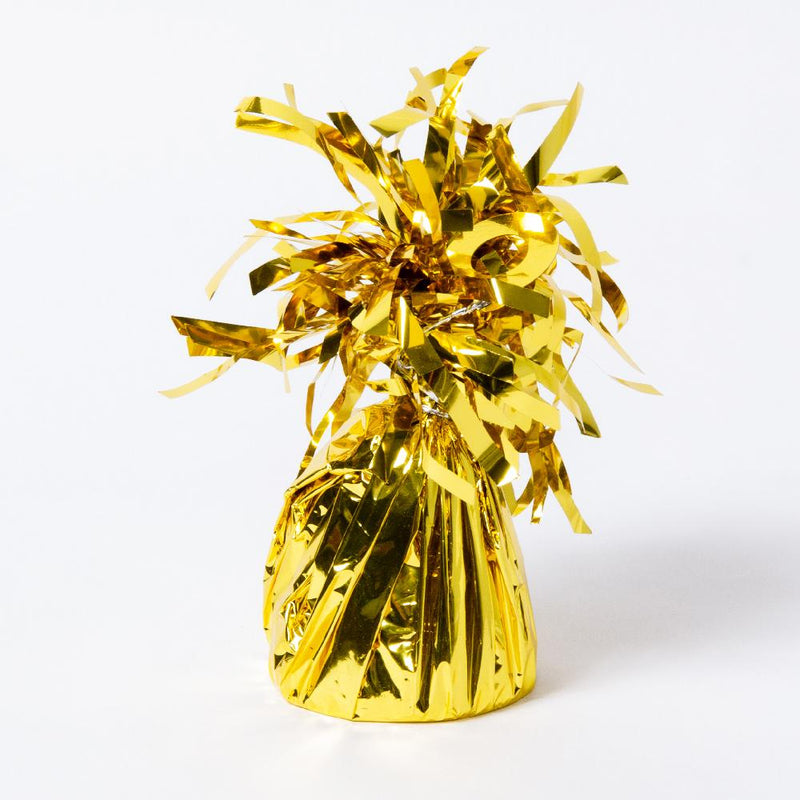 A gold foil balloon weight with fluttery tassels on top