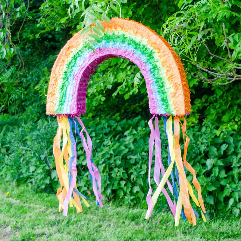 A large, colourful rainbow party pinata with tassel streamers