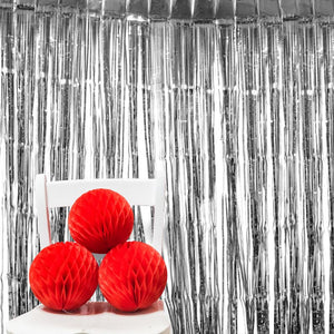 A metallic silver foil curtain with red pom poms