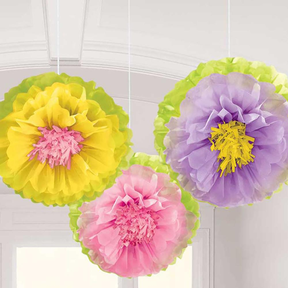 3 fluffy flower pom pom decorations hanging from a party ceiling