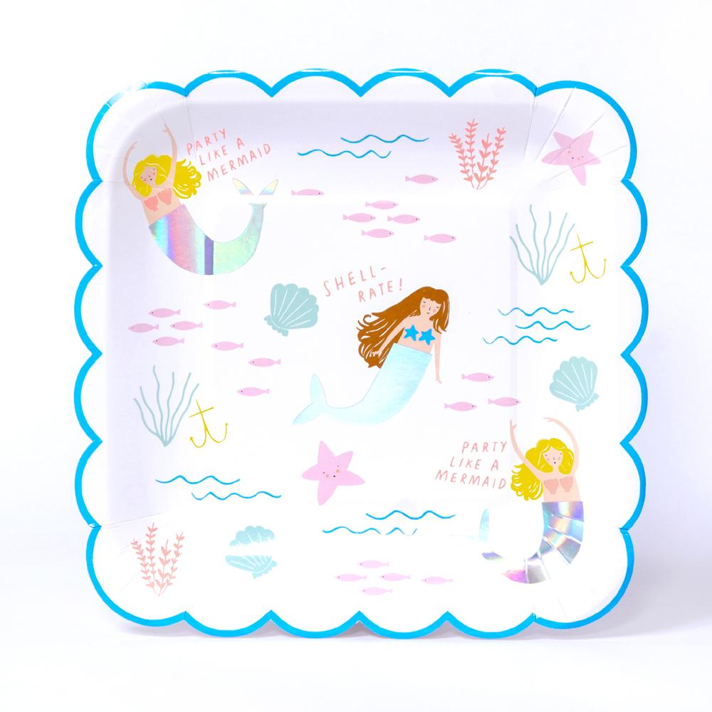 A scalloped-edged mermaid party plate with a blue rim and ocean-themes