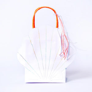 A party gift bag with a clamshell-shape, tassel, and bright orange handle