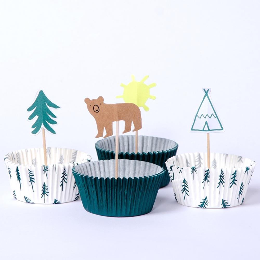 A group of cupcake cases and woodland-themed cake toppers