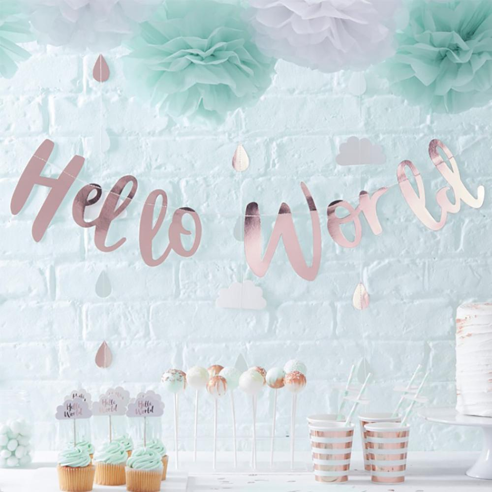 A rose gold baby shower banner hung up above a party table