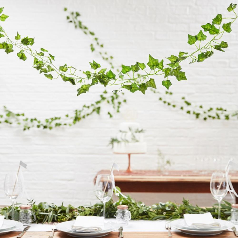 A green vine leaf garland hung above a party table