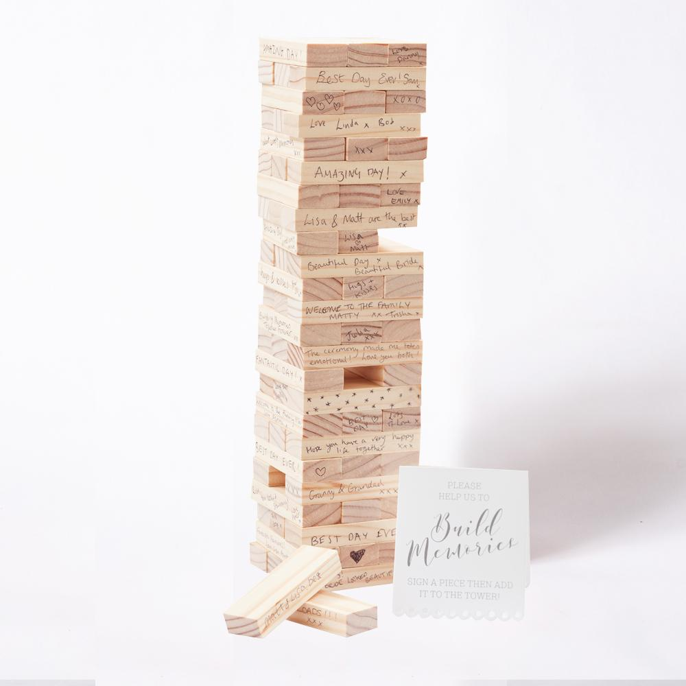 A large wooden brick tower with wedding guest messages written on each brick