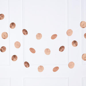 A rose gold party garland featuring a number of rose gold foil polkadots