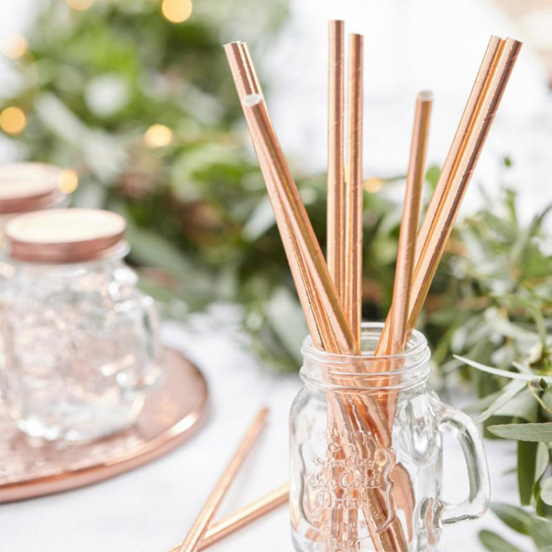 A glass jar filled with shiny, rose gold-foiled paper party straws