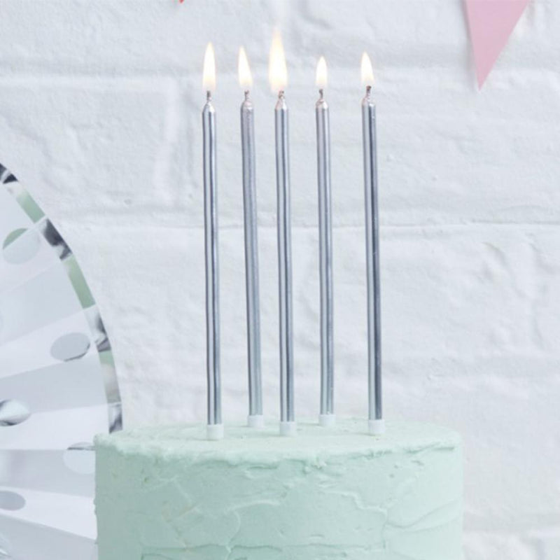 5 tall, silver-foiled cake candles on top of a party cake