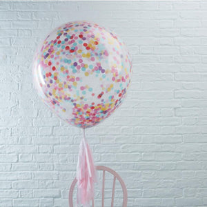 A large clear latex balloon filled with rainbow-coloured confetti