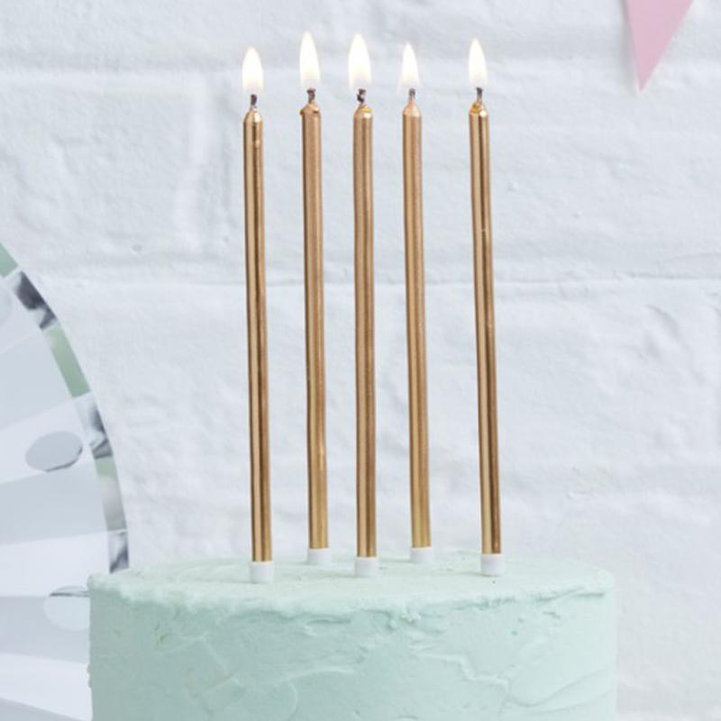5 Rose gold cake candles placed on top of a mint-coloured cake