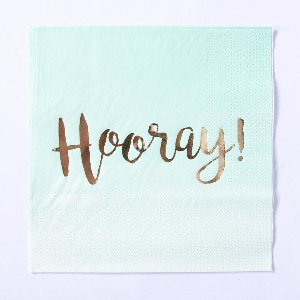 "A pastel green party napkin with the phrase ""Hooray!"" written on in gold foil text"