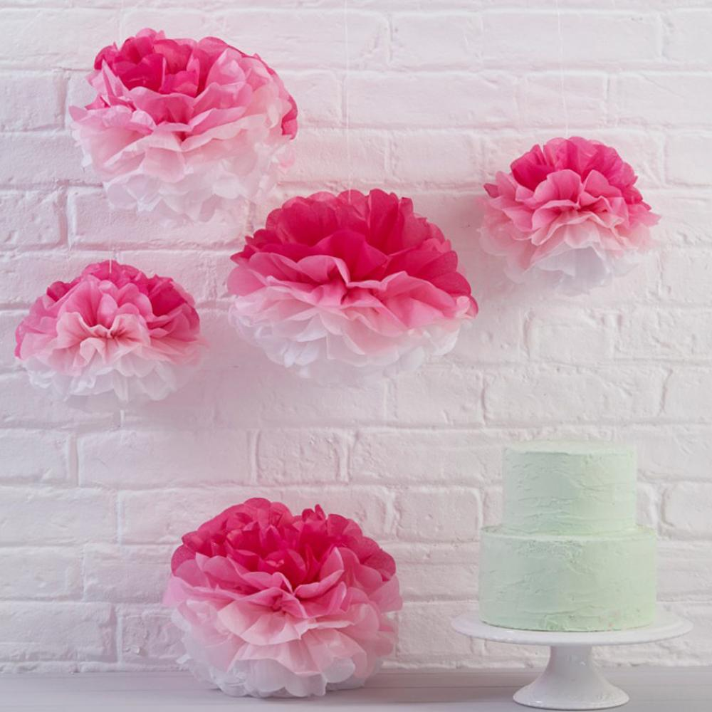 A collection of 5 fluffy pink paper pom poms hanging over a party table