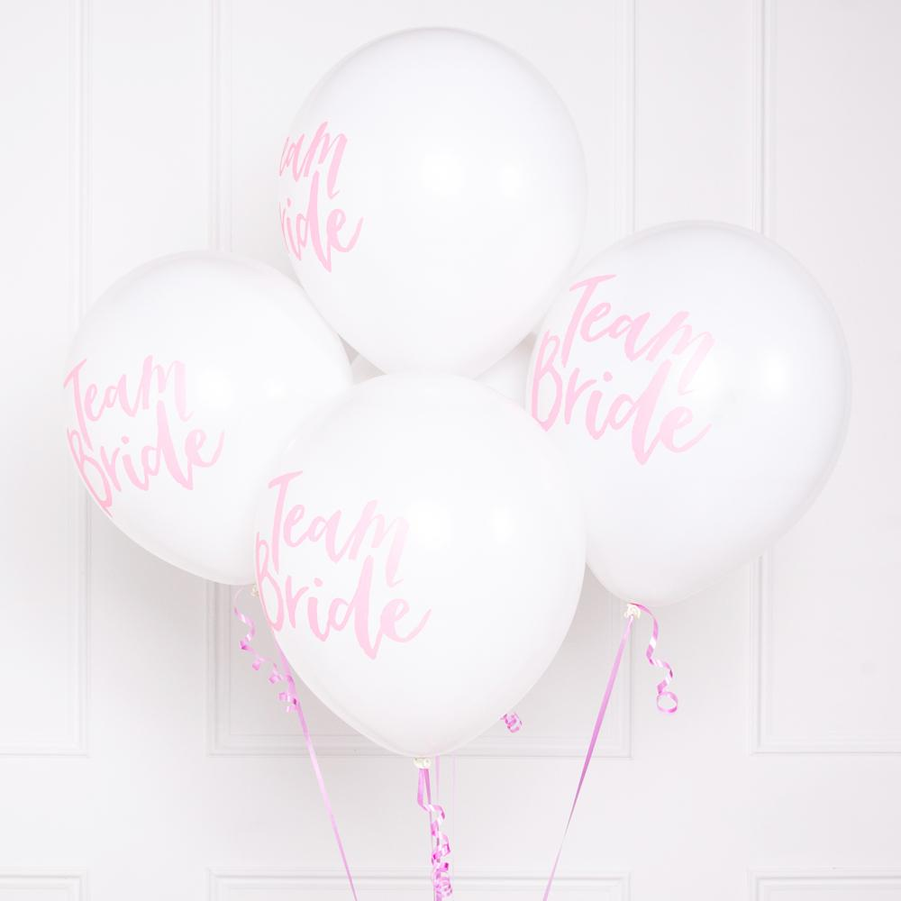"A bunch of white and pink hen party balloons with a ""Team Bride"" phrase in cursive font"