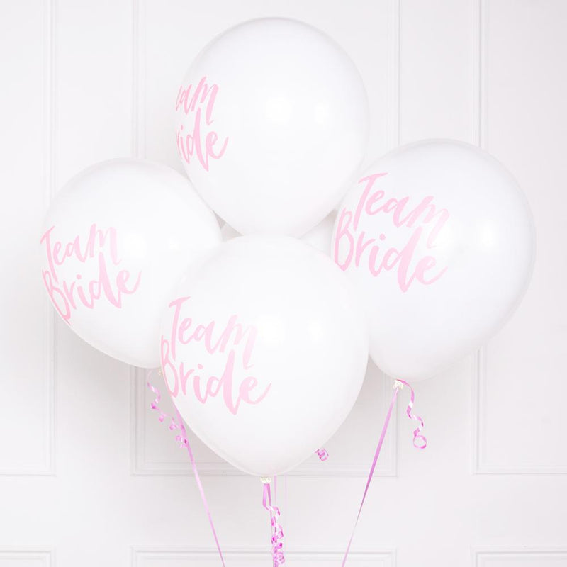 A bunch of white and pink hen party balloons with a