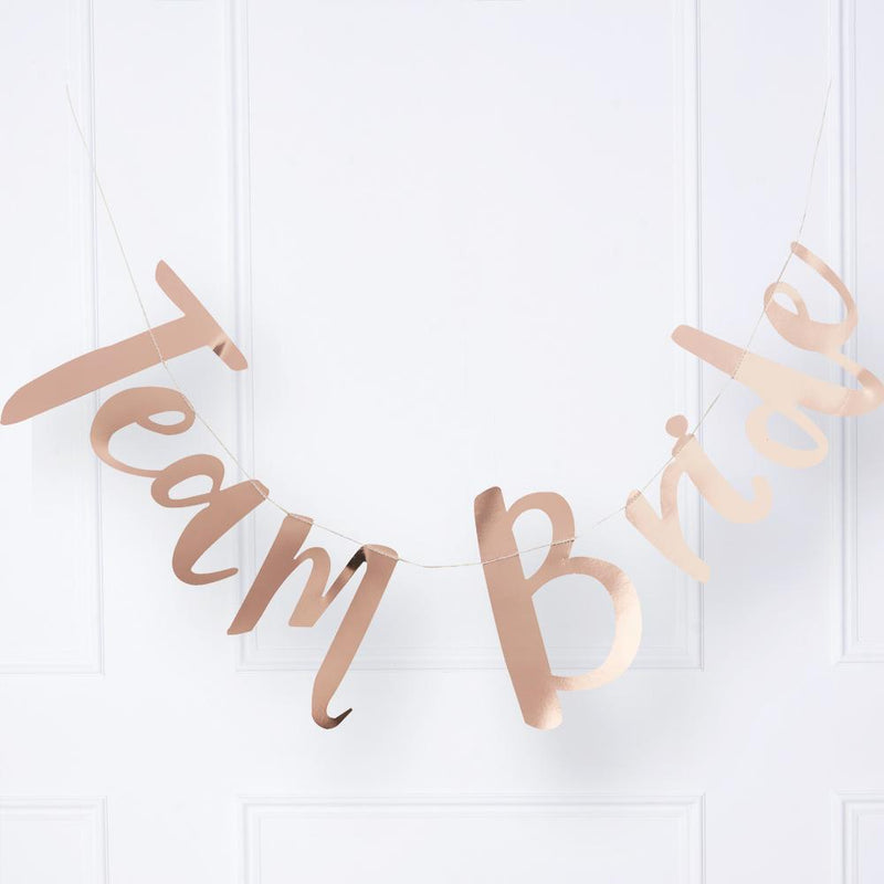 "A hen party banner with the phrase ""Team Bride"" written in rose gold foil text"