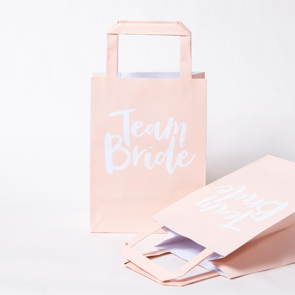 Pink Hen party gift bags with Team Bride written in white cursive font