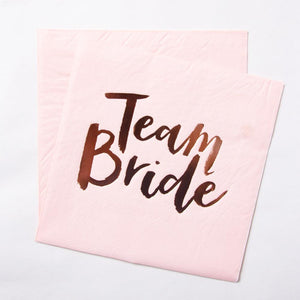 "2 pastel pink hen party napkins with a ""Team Bride"" phrase written in rose gold foil"