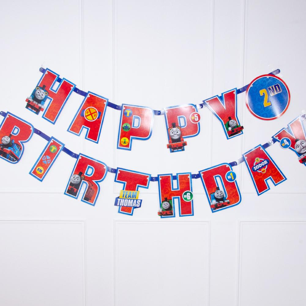A Thomas the Tank Engine birthday party banner with red letters and characters from the show