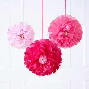 3 pink paper party pom poms hanging from the ceiling