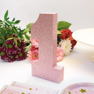 A large pink number 1 party centrepiece covered in sparkling glitter