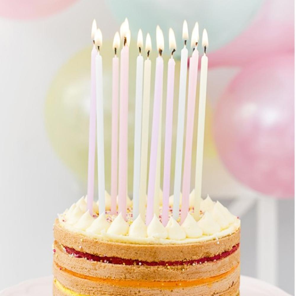A birthday cake with tall wax candles placed on top