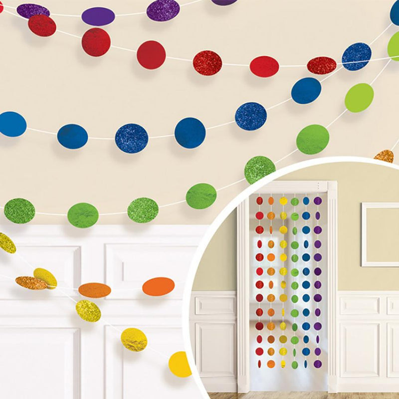 A collection of glittery rainbow-coloured polkadot bunting hung around a party room