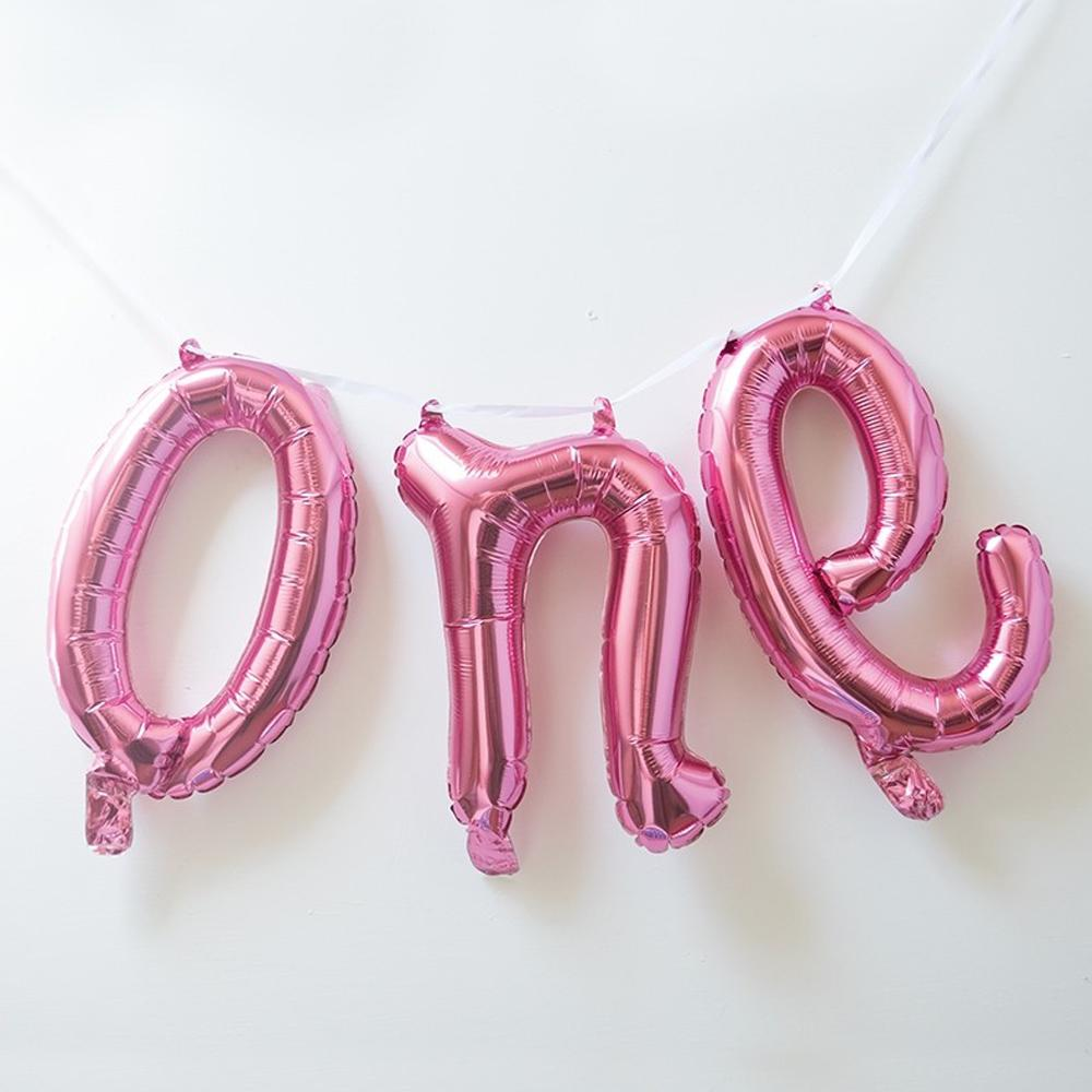 "A pink foil 1st birthday balloon banner saying ""One"""