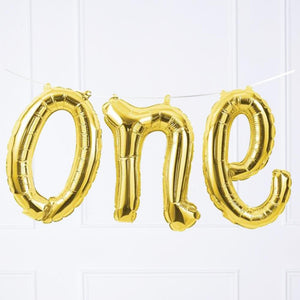 "A gold balloon banner with the word ""one"" written in a cursive font"