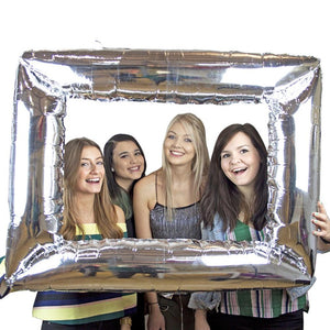 An inflatable silver photoframe with a group of women taking a photo