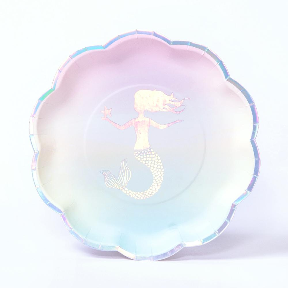 A scallop-edged party plate with a silver mermaid badge on a pastel gradient background