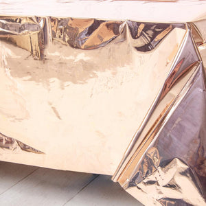 A shiny rose gold-foiled plastic table cover