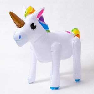 An inflatable party unicorn with gold horn and rainbow-coloured mane