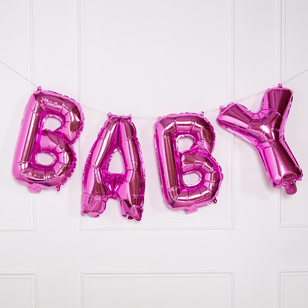 "A pink balloon bunting with the phrase ""BABY"" hanging up on a wall"