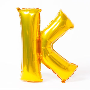 "A shiny metallic gold letter ""K"" balloon"