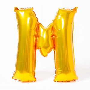 "A shiny metallic gold letter ""M"" balloon"