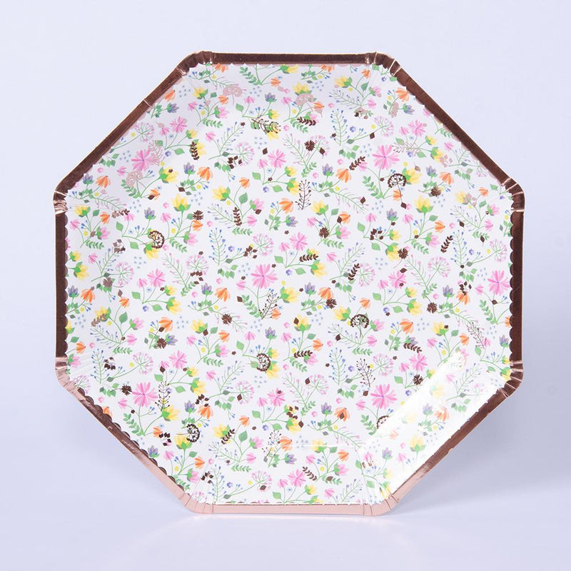 An octagonal party plate with a rose gold trim and floral-patterned design