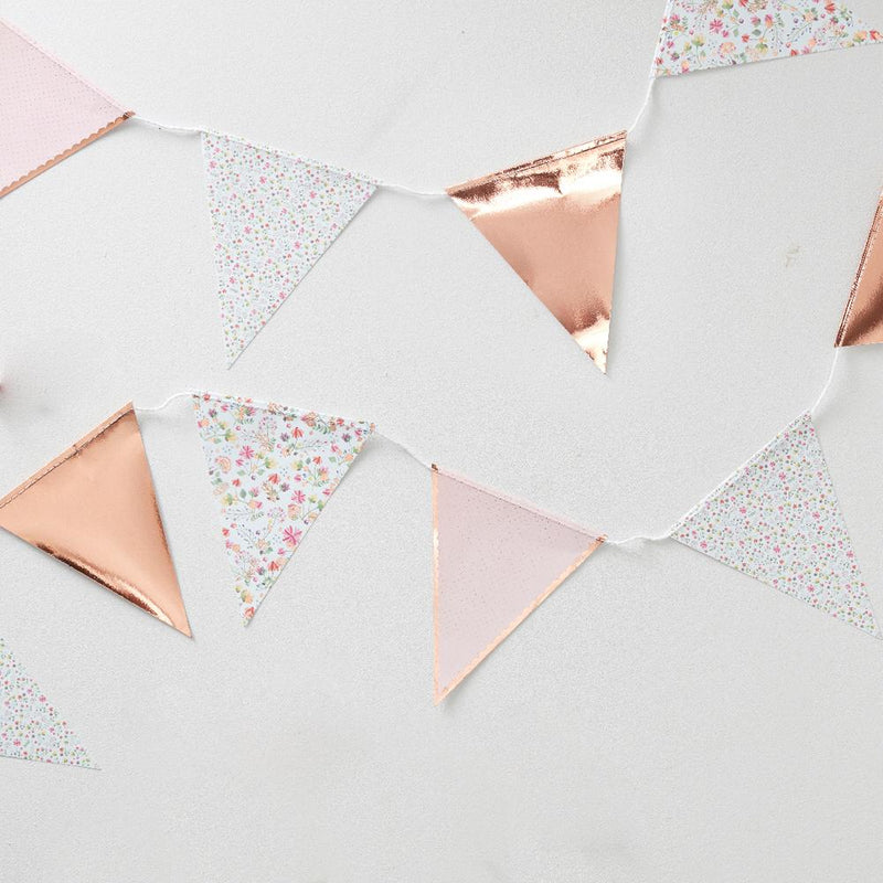 A floral, rose gold decorated paper party bunting laid out on a table
