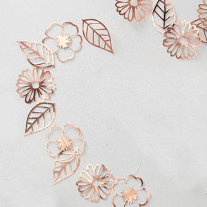 A rose gold garland with flower and leaf-shaped cutouts