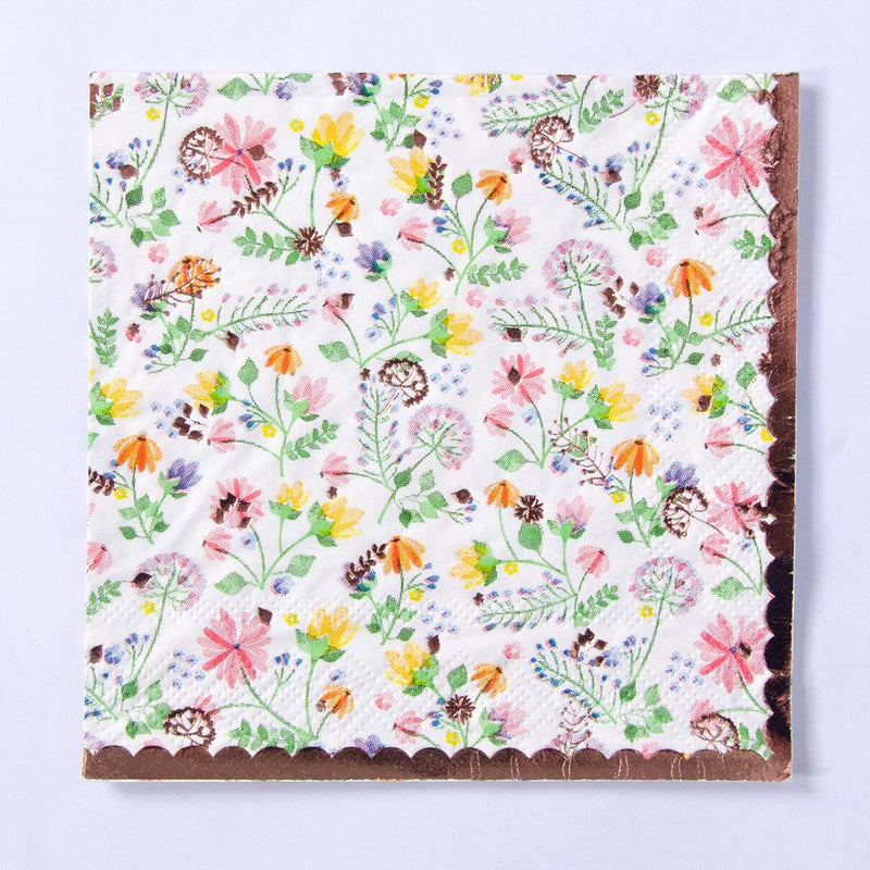 A party napkin with a rose gold trim and floral-patterned design