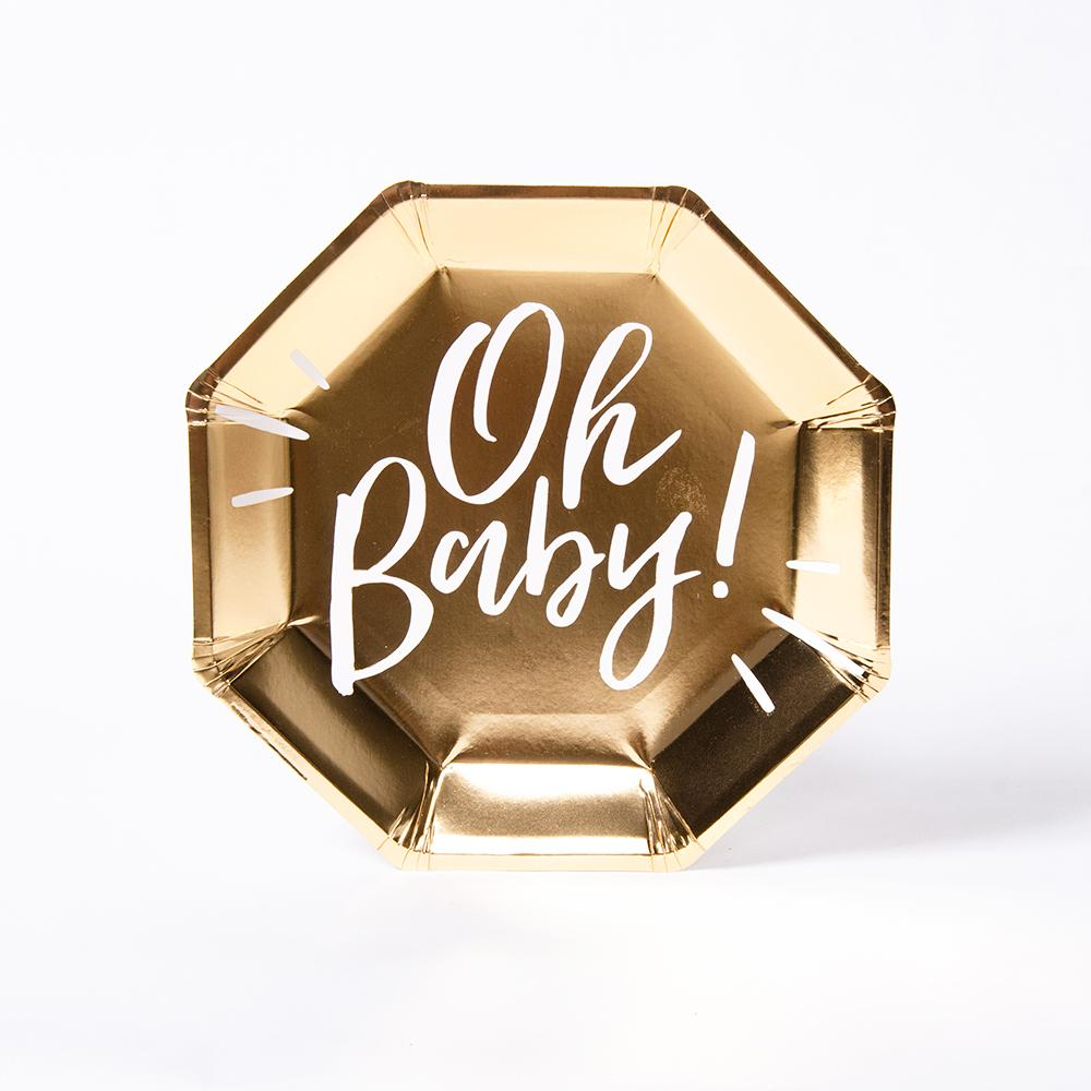 "A gold foil baby shower plate with the phrase ""Oh Baby!"" written in white lettering"