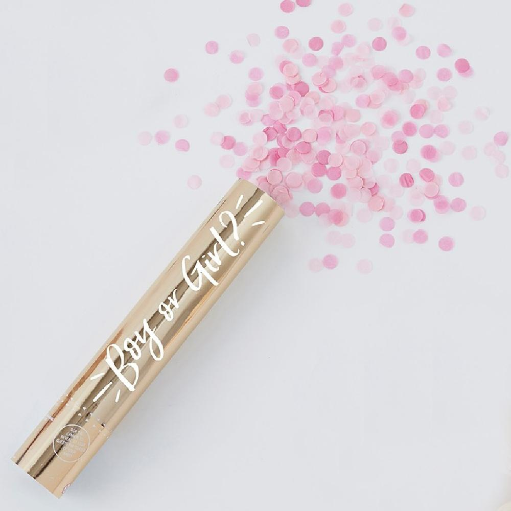 A gold gender reveal confetti cannon with a burst of pink confetti shooting out the top