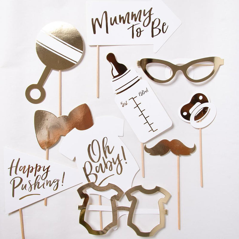 A collection of baby shower party photo booth props laid out on a white background