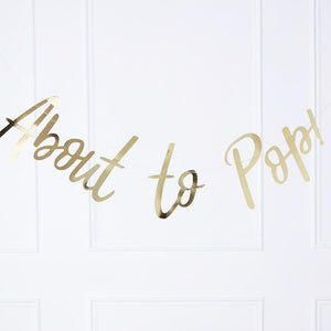 "A gold foil baby shower banner with the phrase ""About to pop!"""