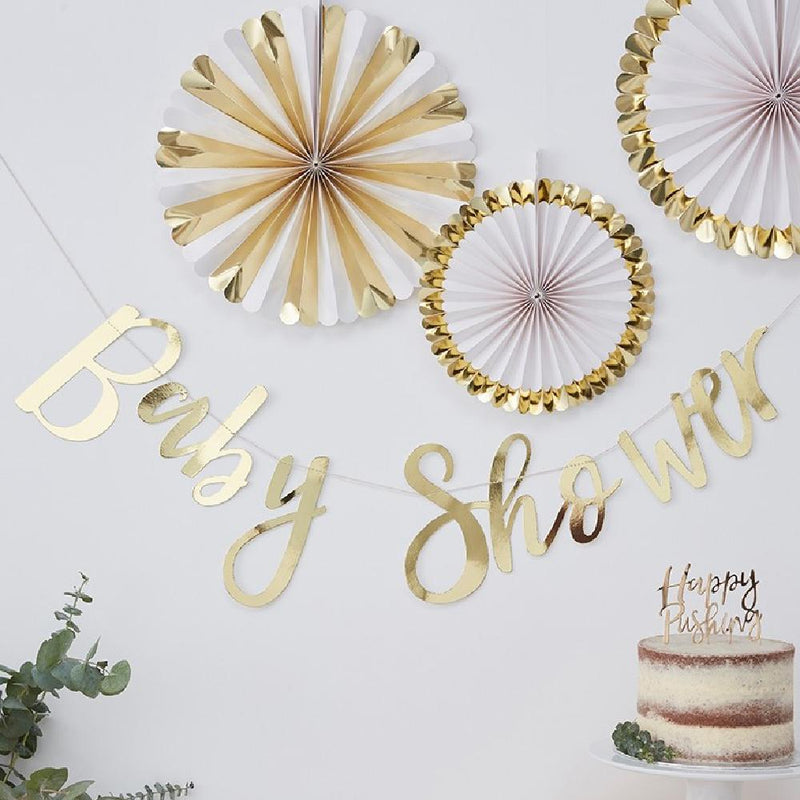 "A gold foil ""Baby Shower"" banner"