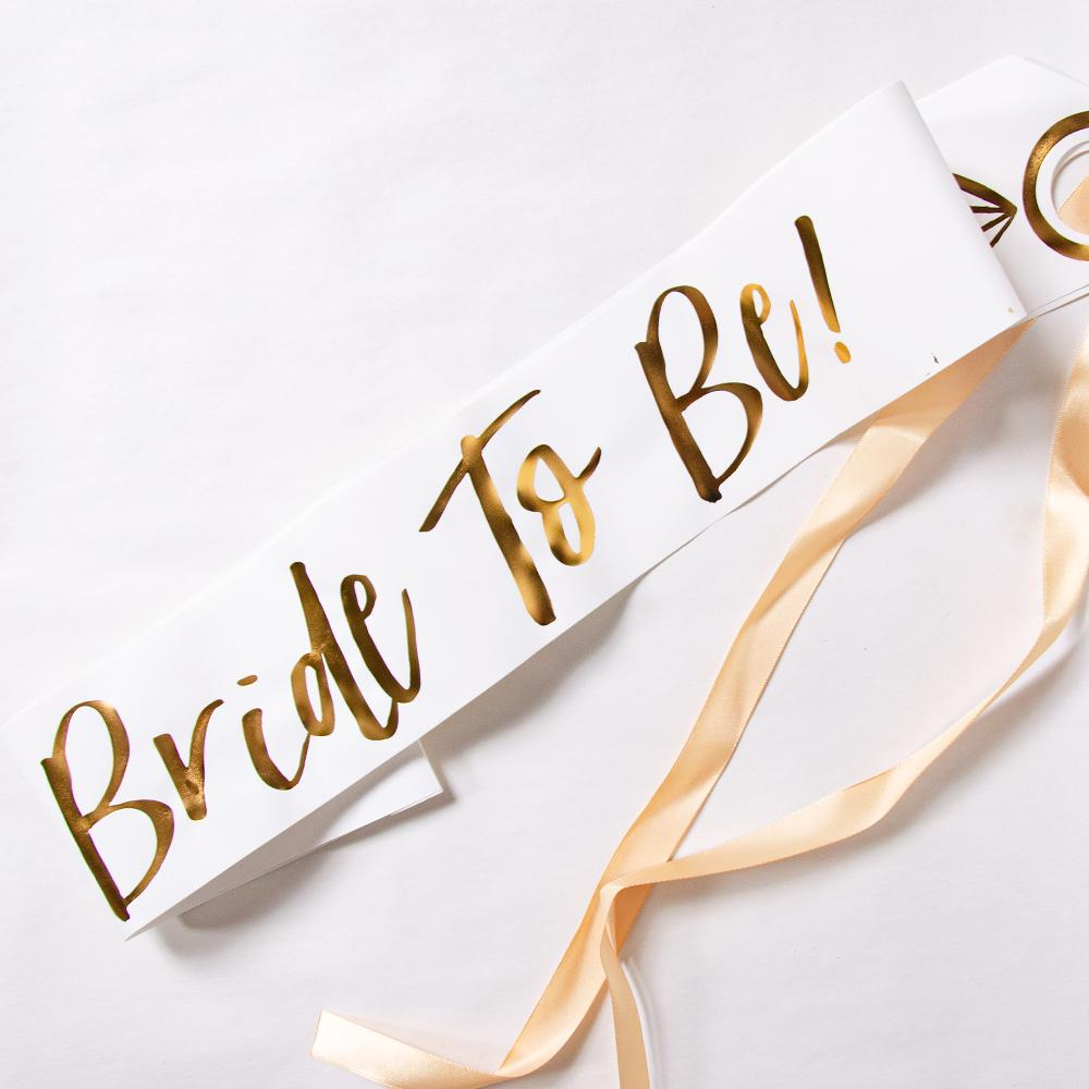 "White and Gold foil ""Bride to Be"" hen party sash on white background"