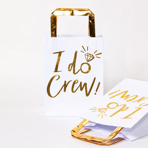 "2 white and gold hen party gift bags with ""I Do Crew!"" phrase written in gold foil writing"