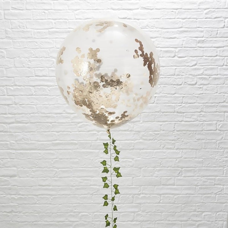 A large clear party balloon filled with rose gold confetti
