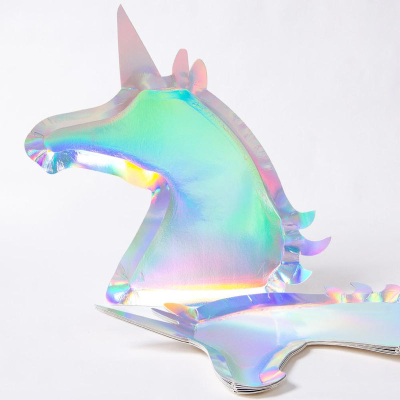 A unicorn-shaped party plate placed on a party table with confetti